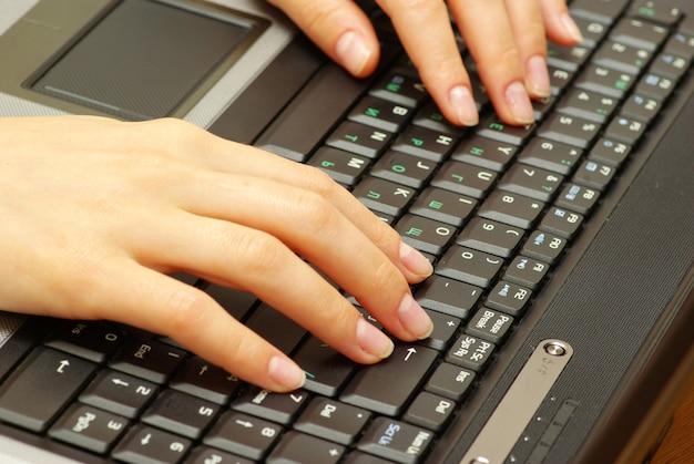 Weibliche hände, die auf laptop-tastatur tippen