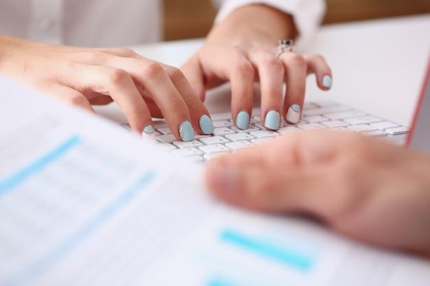Weibliche hände, die auf silberner tastatur unter verwendung des computers tippen