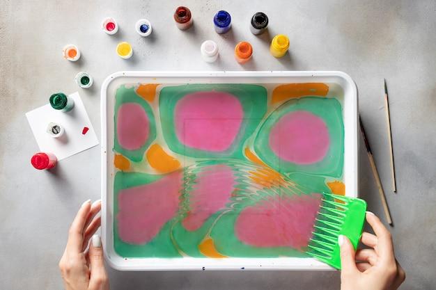 Weibliche hände, die auf wasser mit farben zeichnen. ebru kunst