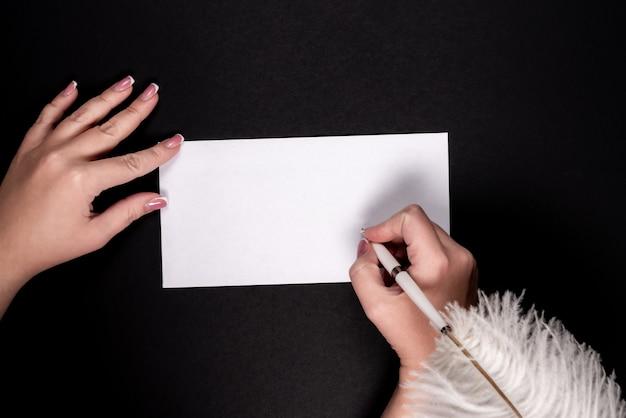 Weibliche hände, die auf weißbuch mit feder vitage stift mit copyspace schreiben