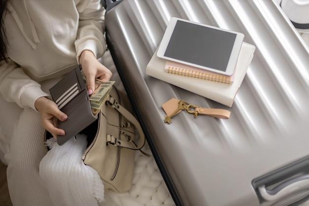 Weibliche hände, die bargelddollar in der brieftasche mit karten halten, bereiten reiseurlaub oder geschäftsreise vor