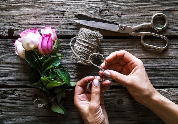Weibliche hände, die den blumenstrauß auf holztisch mit rose machen. blumen