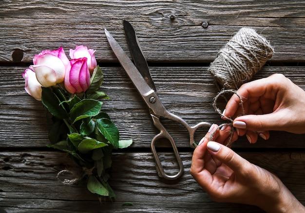 Weibliche hände, die den blumenstrauß auf holztisch mit rosen machen