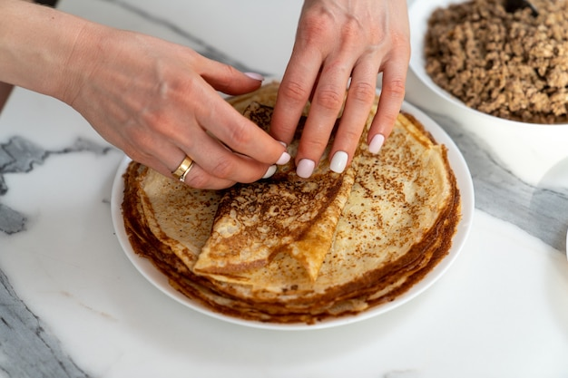 Weibliche hände, die die fleischfüllung in einen pfannkuchen einwickeln