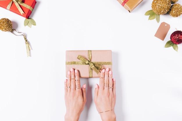 Weibliche hände, die die geschenke des neuen jahres einwickeln