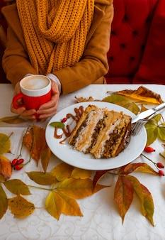 Weibliche hände, die die rote tasse kaffee nahe kuchen mit herbstlaubhintergrund halten