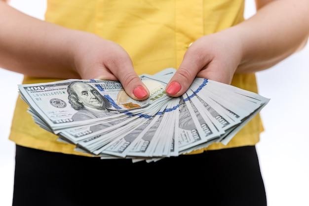 Weibliche hände, die dollarbanknoten im fächer halten