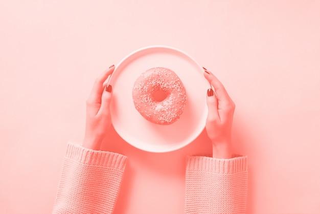 Weibliche hände, die donut auf platte halten