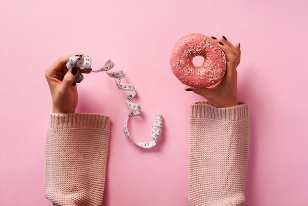 Weibliche hände, die donut halten und band über rosa hintergrund messen.