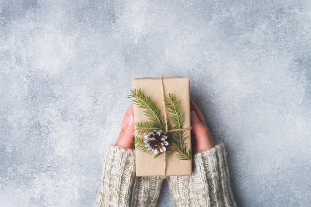 Weibliche hände, die ein eingewickeltes geschenk für weihnachten auf grau halten