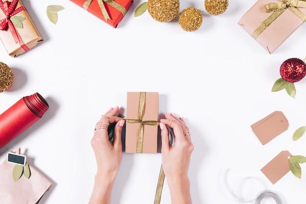 Weibliche hände, die ein geschenk einwickeln