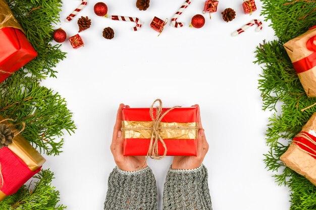 Weibliche hände, die ein geschenk mit einer roten schleife auf einem weißen raum mit einem neujahrsdekorateur halten
