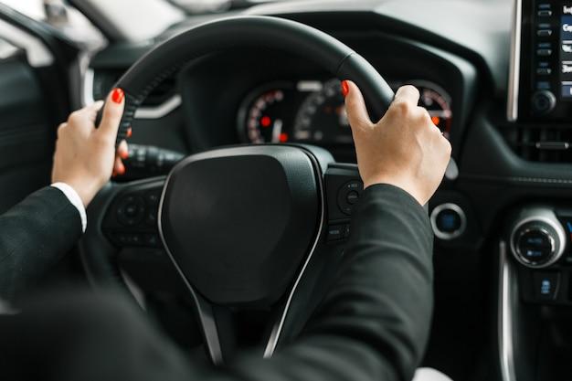 Weibliche hände, die ein lenkrad im autosalon halten.