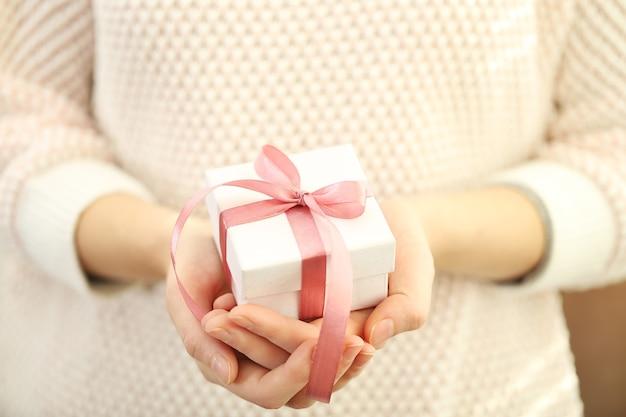 Weibliche hände, die ein schönes kleines geschenk halten, das mit satinband umwickelt ist.