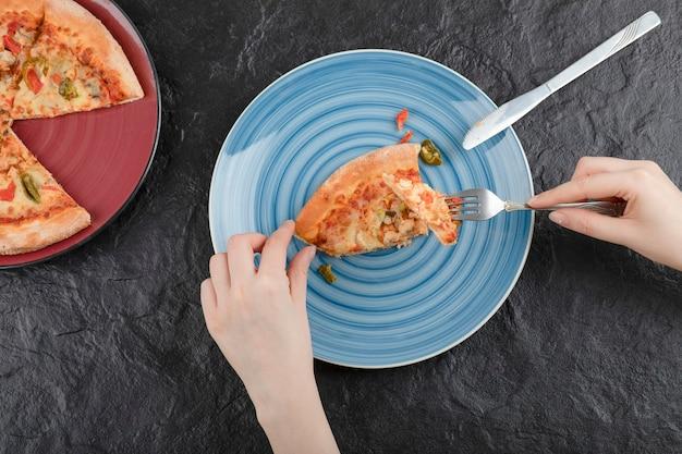 Weibliche hände, die ein stück pizza vom teller auf schwarzem hintergrund nehmen.