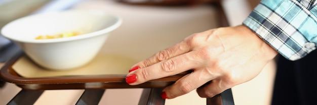 Weibliche hände, die ein tablett mit einer portion essen in der café-nahaufnahme halten