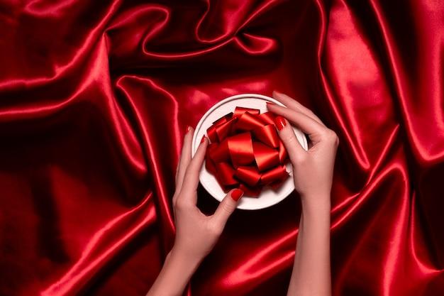 Weibliche hände, die eine festliche schachtel mit bändern und schleifen halten. roter festlicher hintergrund oben horizontale ansicht copyspace.