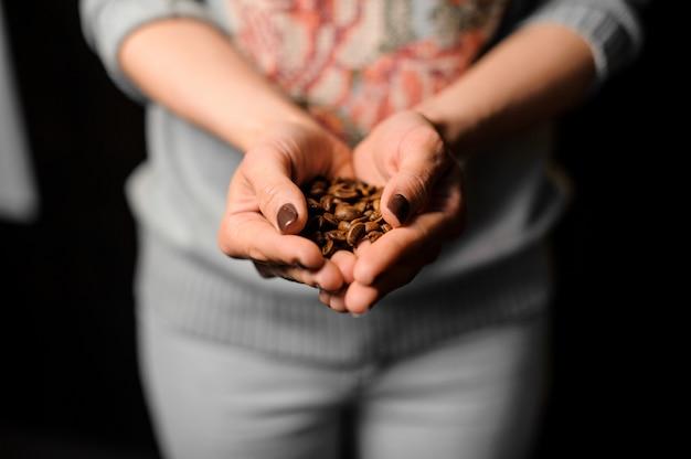 Weibliche hände, die eine handvoll frische kaffeebohnen halten