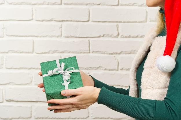Weibliche hände, die eine kleine geschenkbox halten, die in packpapier eingewickelt wird. geschenke von geliebten menschen geben und empfangen