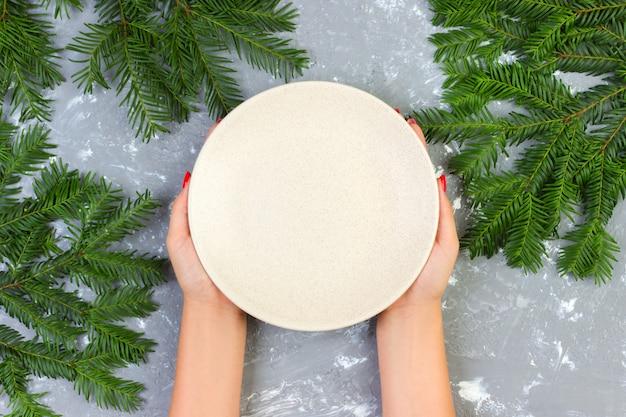 Weibliche hände, die eine leere weiße platte auf einer grauen oberfläche mit weihnachten halten, verzweigen sich
