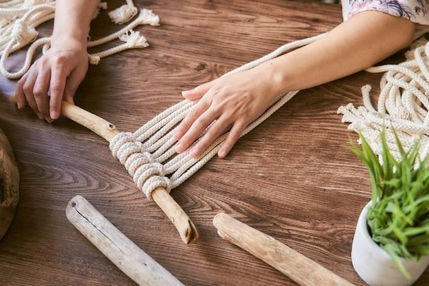 Weibliche hände, die eine makramee-dekoration auf einem hölzernen schreibtisch arbeiten