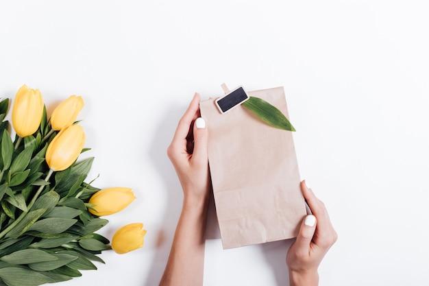Weibliche hände, die eine papiertüte mit einem geschenk nahe dem blumenstrauß von gelben tulpen auf einem weißen hintergrund halten