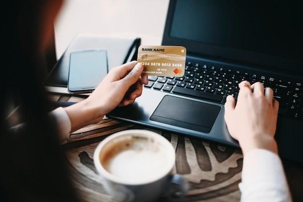 Weibliche hände, die eine plastikkreditkarte und einen laptop für online-transaktion verwenden, während sie in einem café nahe einem fenster sitzen.