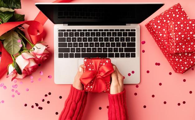 Weibliche hände, die eine rote valentinsgruß-geschenkbox-draufsicht auf rosa hintergrund halten