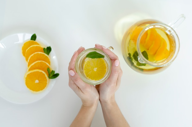 Weibliche hände, die eine schale detoxtee mit orange frucht und minze auf whitw hintergrund halten.