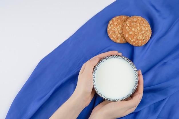 Weibliche hände, die eine schüssel milch mit haferkeksen auf einer blauen tischdecke halten.