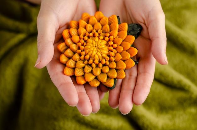 Weibliche hände, die eine seife in einer form der chrysanthemenblume halten.