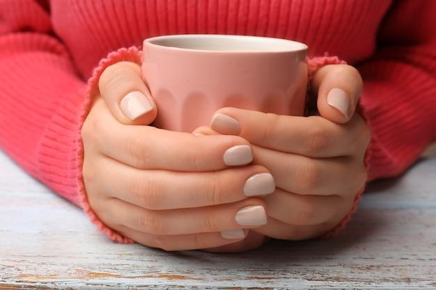 Weibliche hände, die eine tasse kaffee auf einem holztisch in der nähe halten