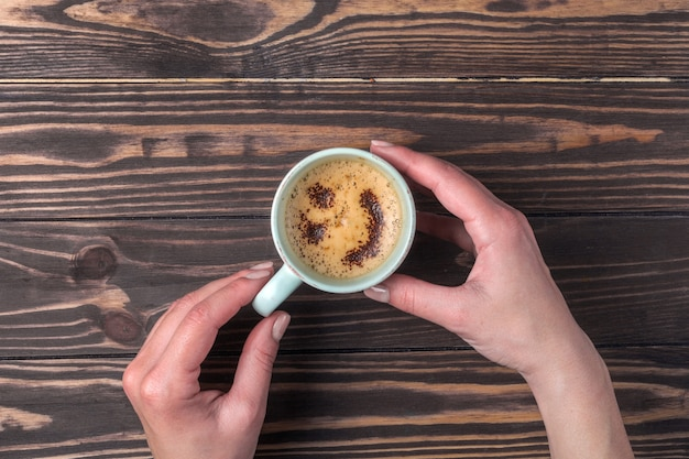 Weibliche hände, die eine tasse kaffee mit schaum über einem holztisch halten. mit schokostreuseln Premium Fotos