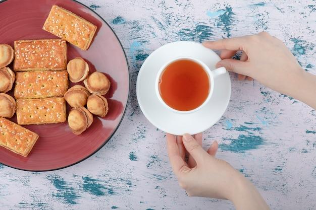 Weibliche hände, die eine tasse tee mit shortbread-nüssen mit kondensmilch halten.