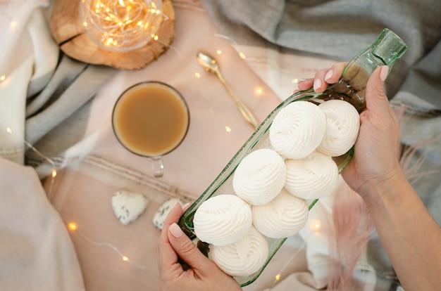 Weibliche hände, die eine ungewöhnliche transparente umhüllungsplatte mit weißen meringen halten. dessert-konzept.