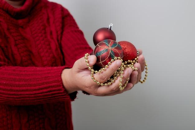 Weibliche hände, die eine weihnachtskugel anhalten