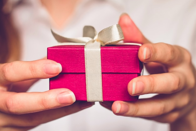 Weibliche hände, die einen kleinen roten kasten mit einem geschenk halten.