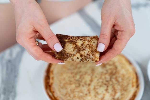 Weibliche hände, die einen pfannkuchen mit der darin eingewickelten füllung halten