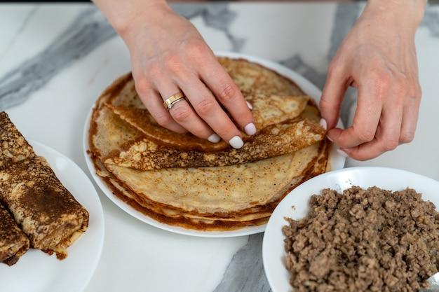 Weibliche hände, die einen pfannkuchen mit fleischfüllung füllen