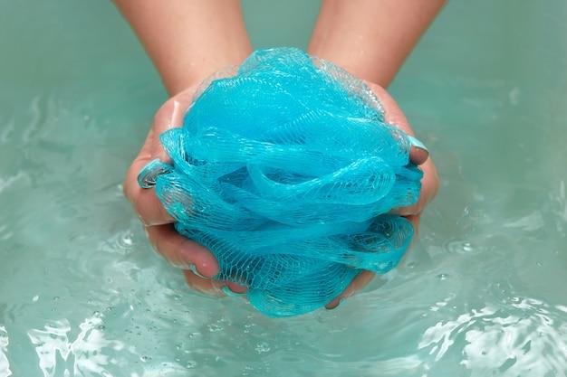 Weibliche hände, die einen runden weichen synthetischen waschlappen im bad mit wasser halten. hände nahaufnahme. spa-behandlung, körperpflege, wasserhintergrund.