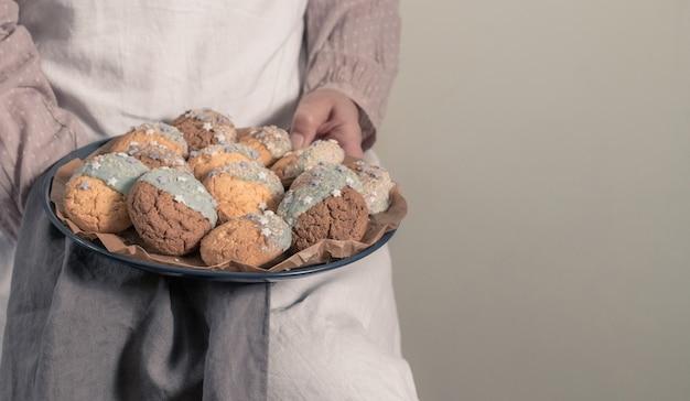Weibliche hände, die einen teller mit keksen für babyparty-partei halten