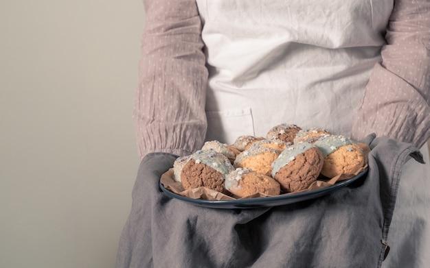 Weibliche hände, die einen teller mit keksen für babyparty-partei halten.