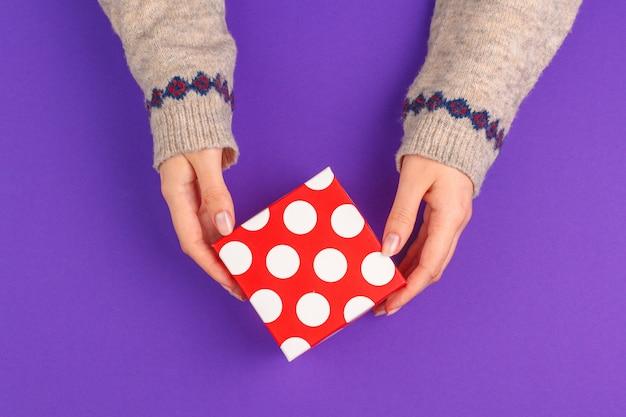 Weibliche hände, die eingewickeltes geschenk auf purpur halten