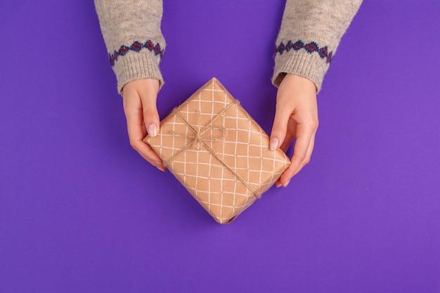 Weibliche hände, die eingewickeltes geschenk auf purpurrotem hintergrund halten