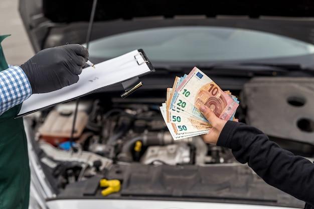 Weibliche hände, die euro-banknoten für autoservice geben