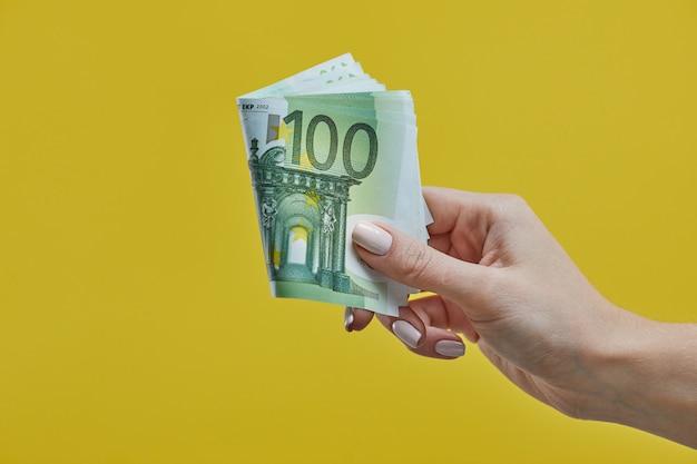 Weibliche hände, die eurobanknoten auf gelb halten