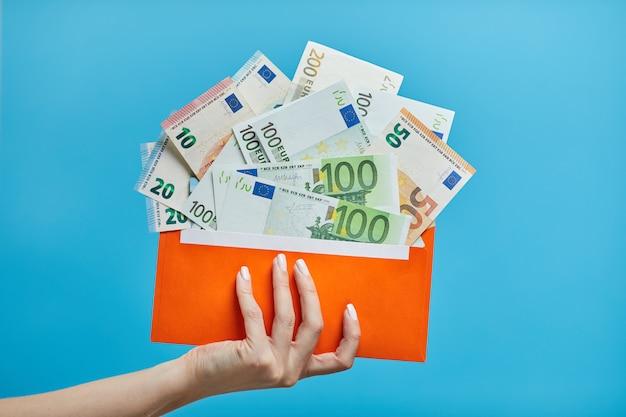 Weibliche hände, die eurobanknoten in einem umschlag halten