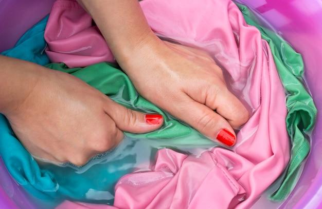 Weibliche hände, die farbkleidung im becken waschen