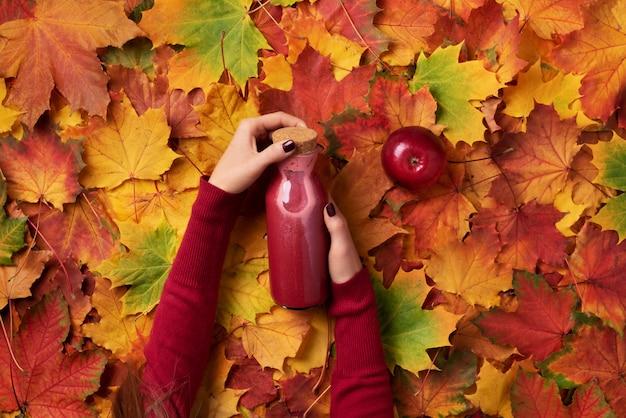 Weibliche hände, die flasche rotes getränk halten