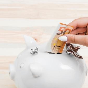 Weibliche hände, die fünfzig euroanmerkung in das weiße piggybank einfügen